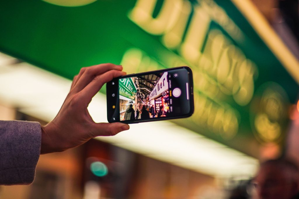 person holding iphone taking a picture in a busy market